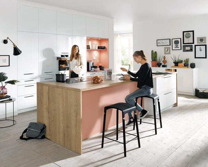 mother and daughter in kitchen, both happy, (white and pink kitchen)