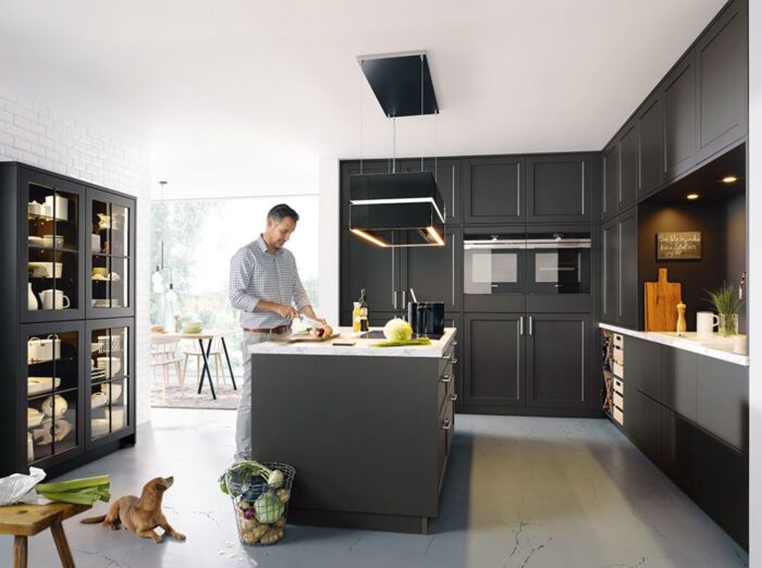 man making food with dog, relaxing in back coloured kitchen